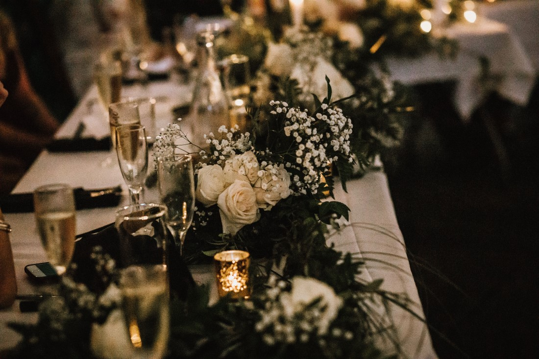 Wedding Head Table with roses, greenery and candles by Flourish Events