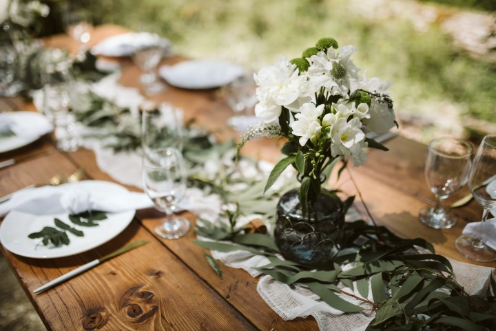 Wood Reception table with greenery and white fabric in the woods
