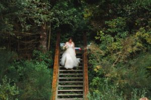 Ocean Wedding Bride walks down stairs to the beach ceremony