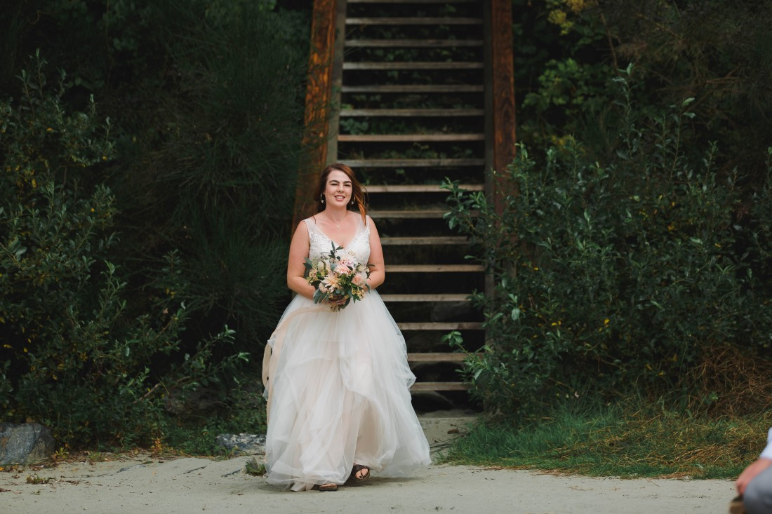 Bride walks towards her wedding ceremony on Tofino beach