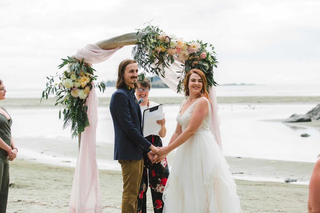 Bride and Groom ceremony in front of arch wrapped in white fabric on Tofino beach