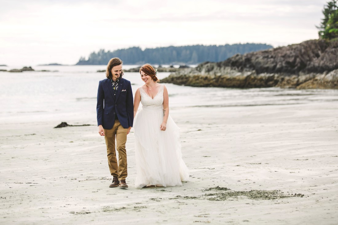 Ocean Wedding Couple walk along beach together in Tofino