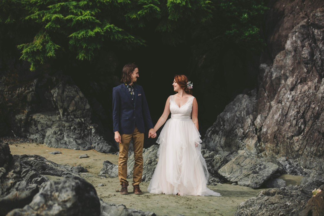 Newlyweds hold hands on Tofino beach by Michelle Milward Photography