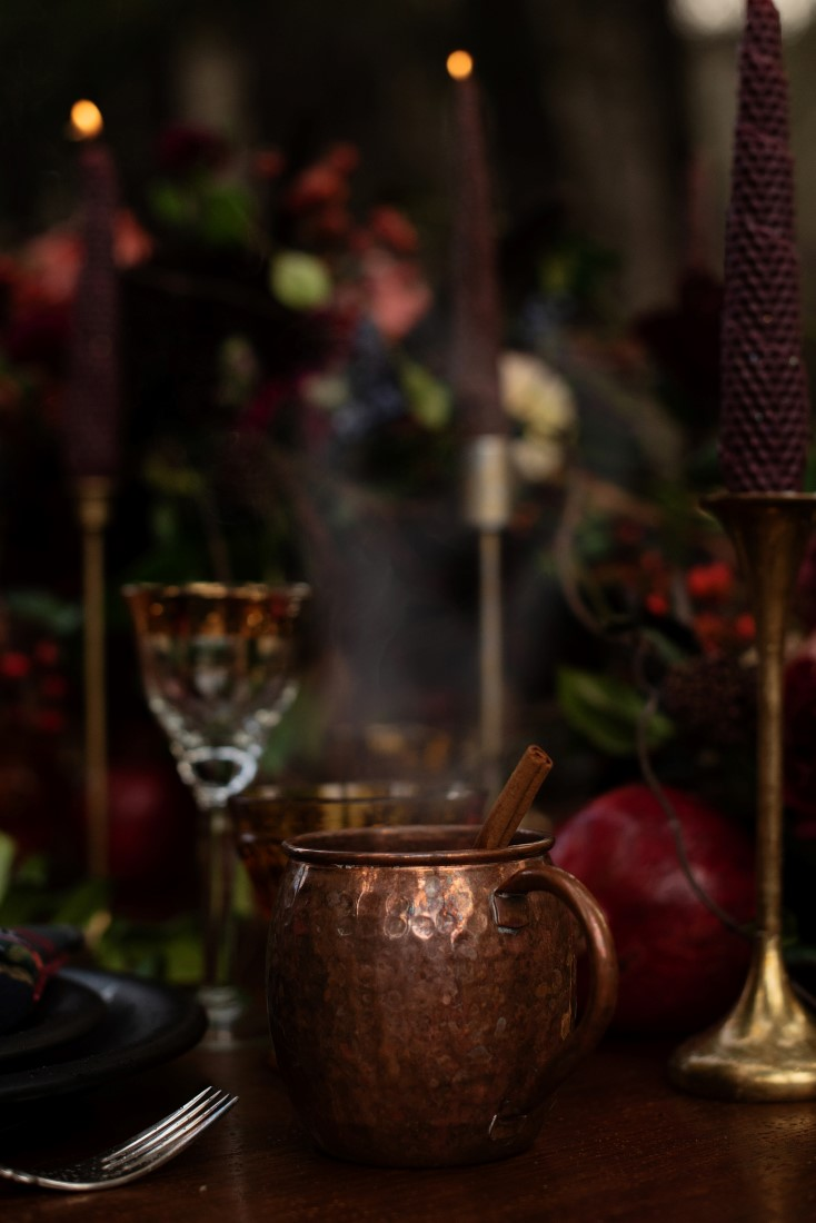 Deep Gold Jar and pomegranate sit on wood table with burgundy taper candles and gold candlesticks
