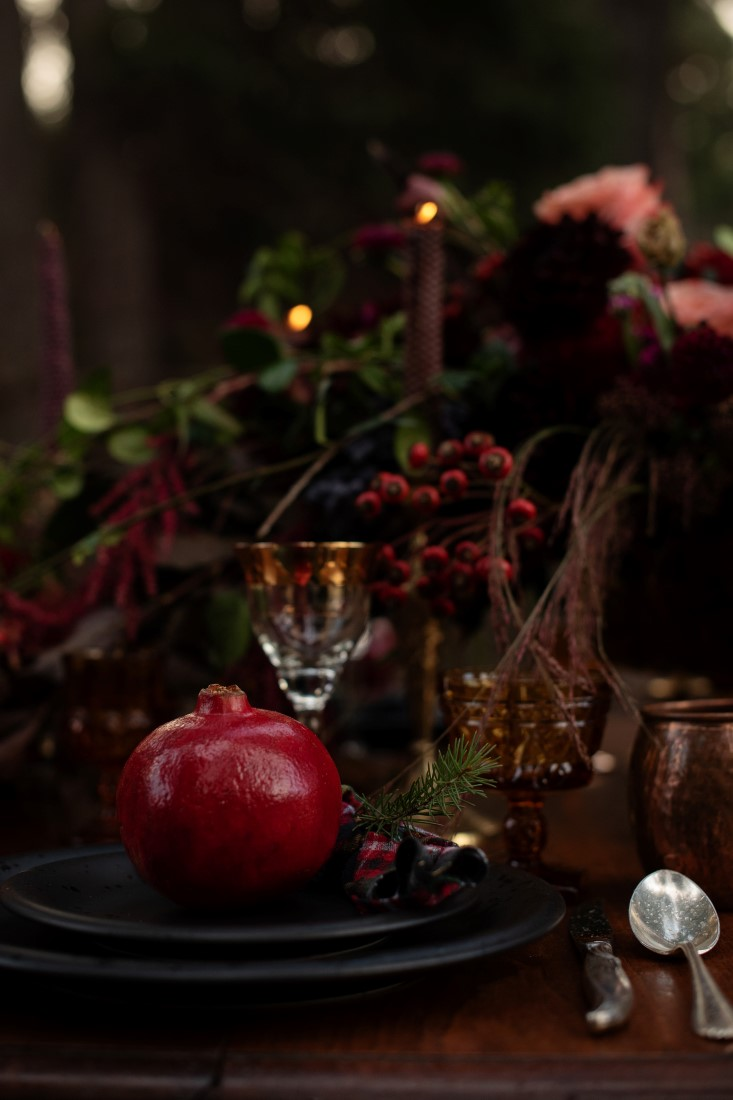 Pomegranate sits on black plates on wedding reception table in the woods
