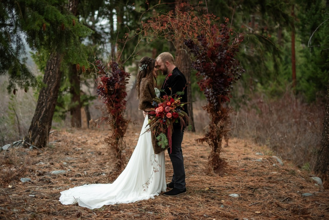 Magical Woodsy Wedding Inspiration couple in front of arch of orange berries by Thistle and Thorne Weddings Vancouver