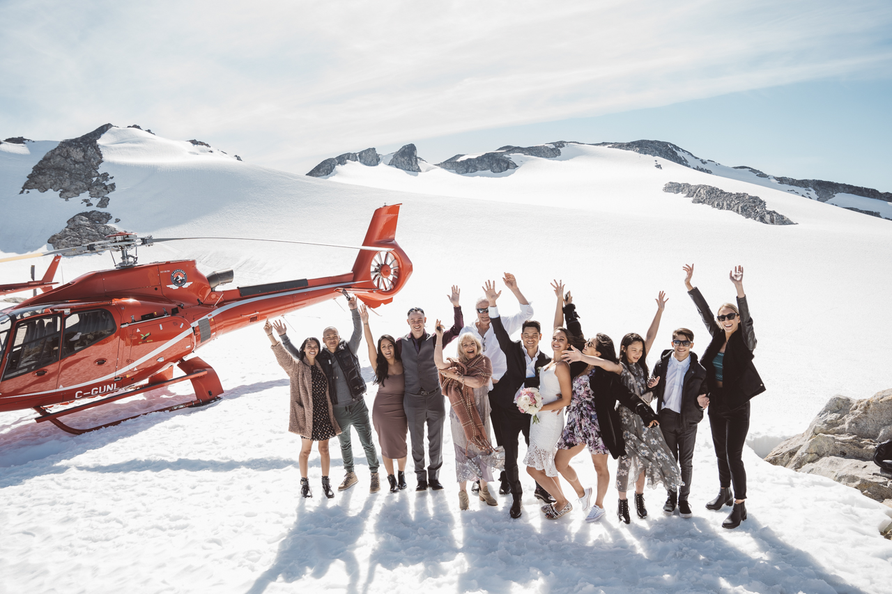 Wedding in the Mountains of Whistler guests stand by helicopter