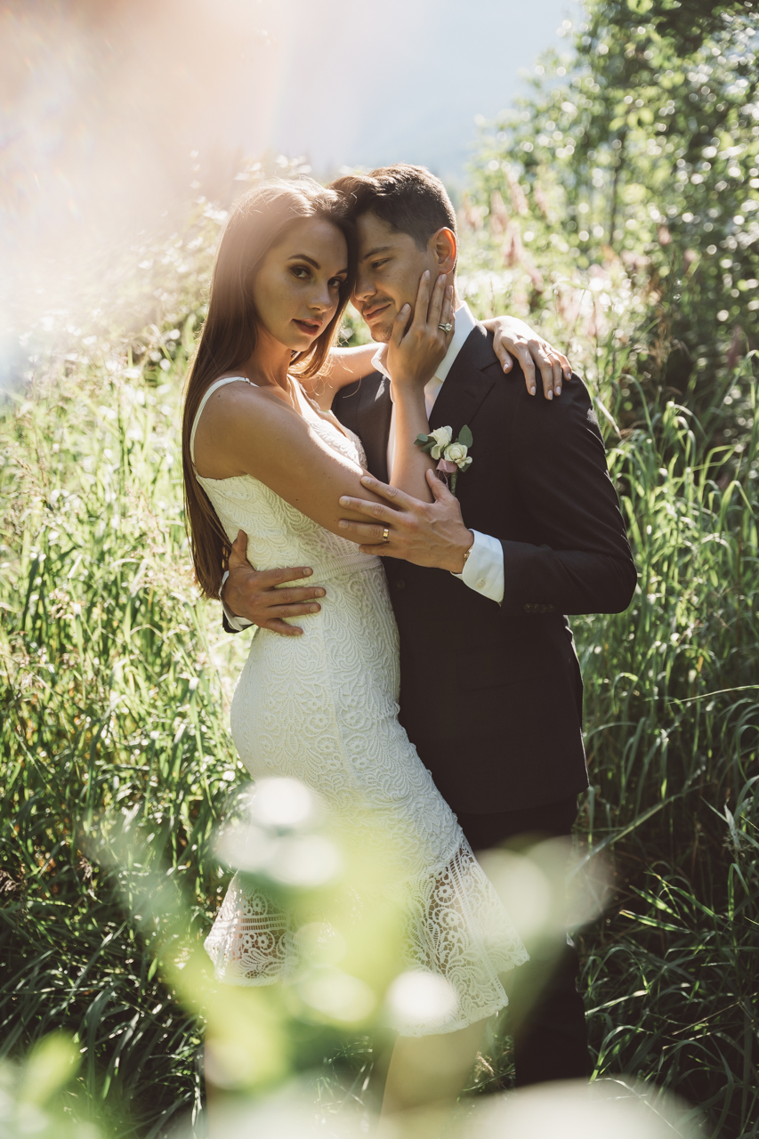 Newlyweds hold each other in long green grass at Whistler