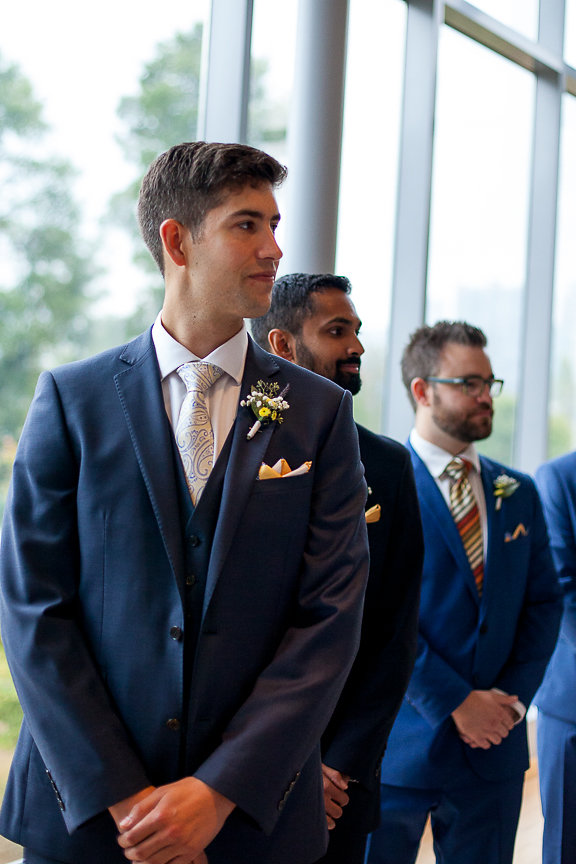 Groom in blue suit awaits bride at the end of aisle at Museum of Vancouver