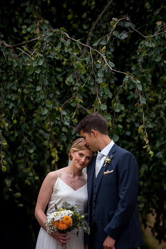 Newlyweds stand in front of trees and smile by Meghan Andrews PHotography