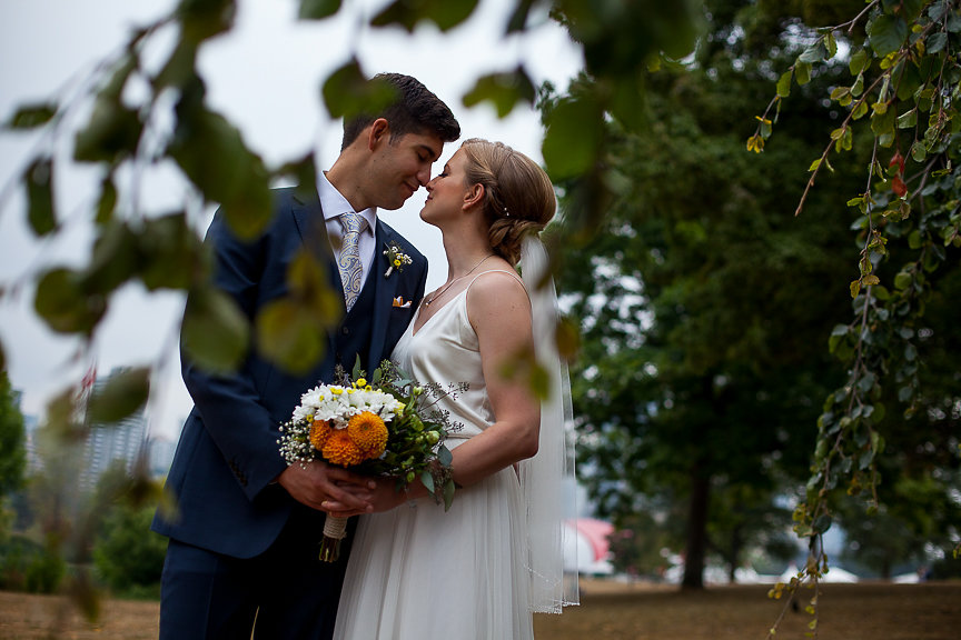Wedding Couple in the trees of Vancouver holding orange and white gerbera daisy bouquet