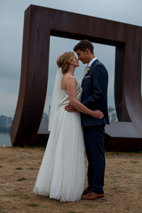 Newlyweds on the beach in front of art installation in Vancouver