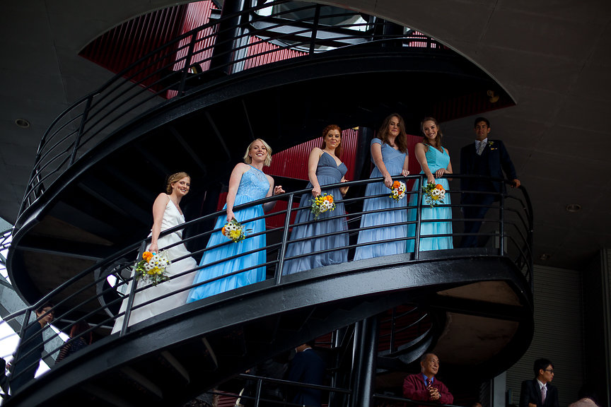 Bridesmaids in blue gowns line an infinity staircase at False Creek Yacht Club Vancouver