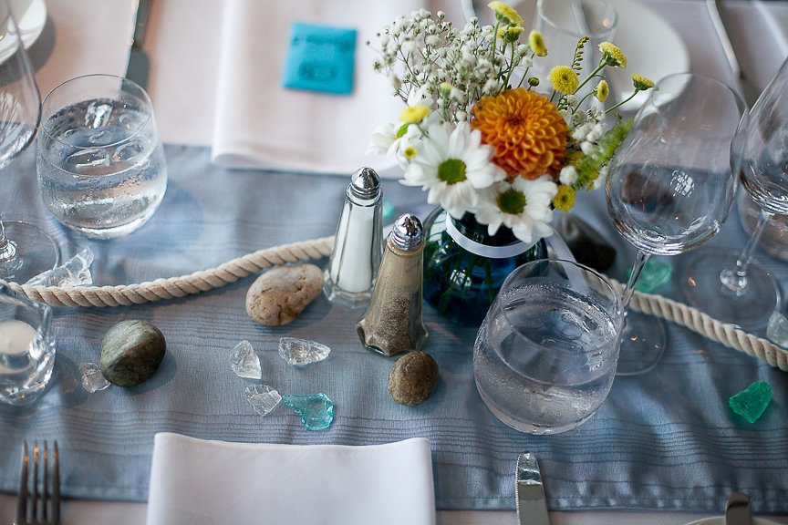 Water themed wedding table with shelles, orange and white gerbera daises