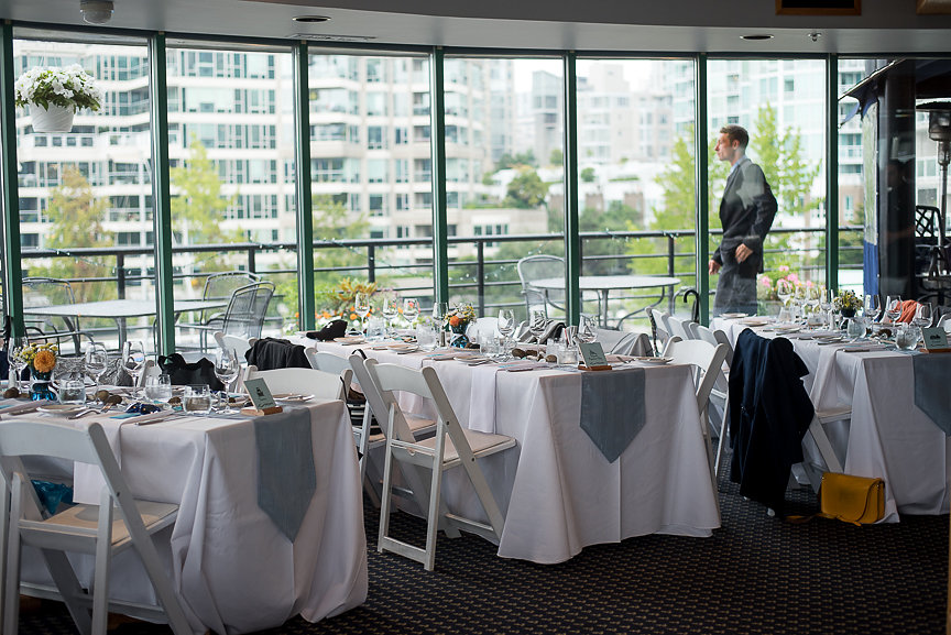 Guest tables in white linen and blue runners in front of bank of windows looking out at water False Creek Yacht Club Vancouver