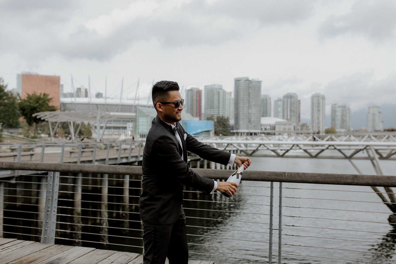 Asian Groom opens champagne bottle on Vancouver water edge