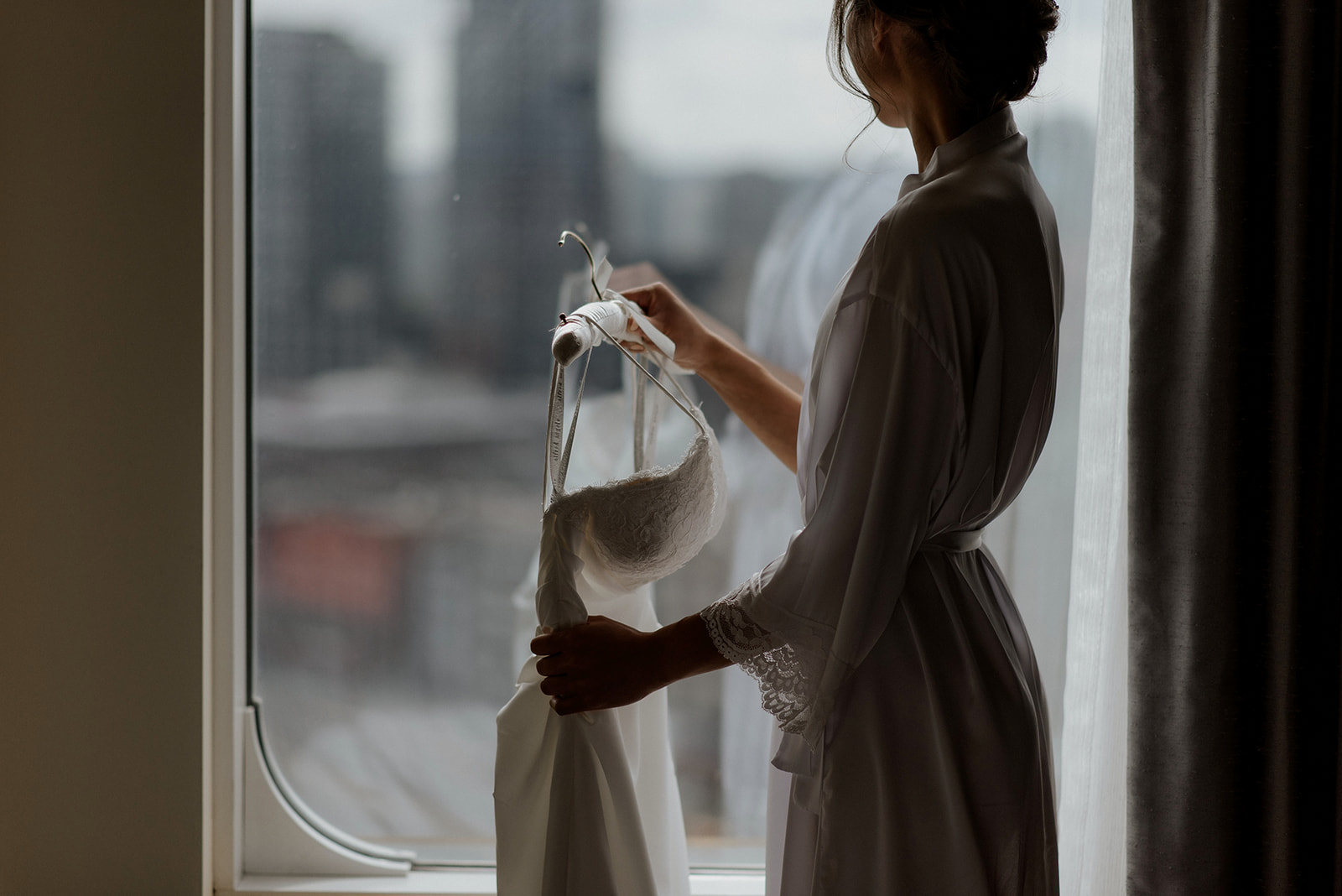 Bride holds her wedding gown in front of Vancouver cityscape