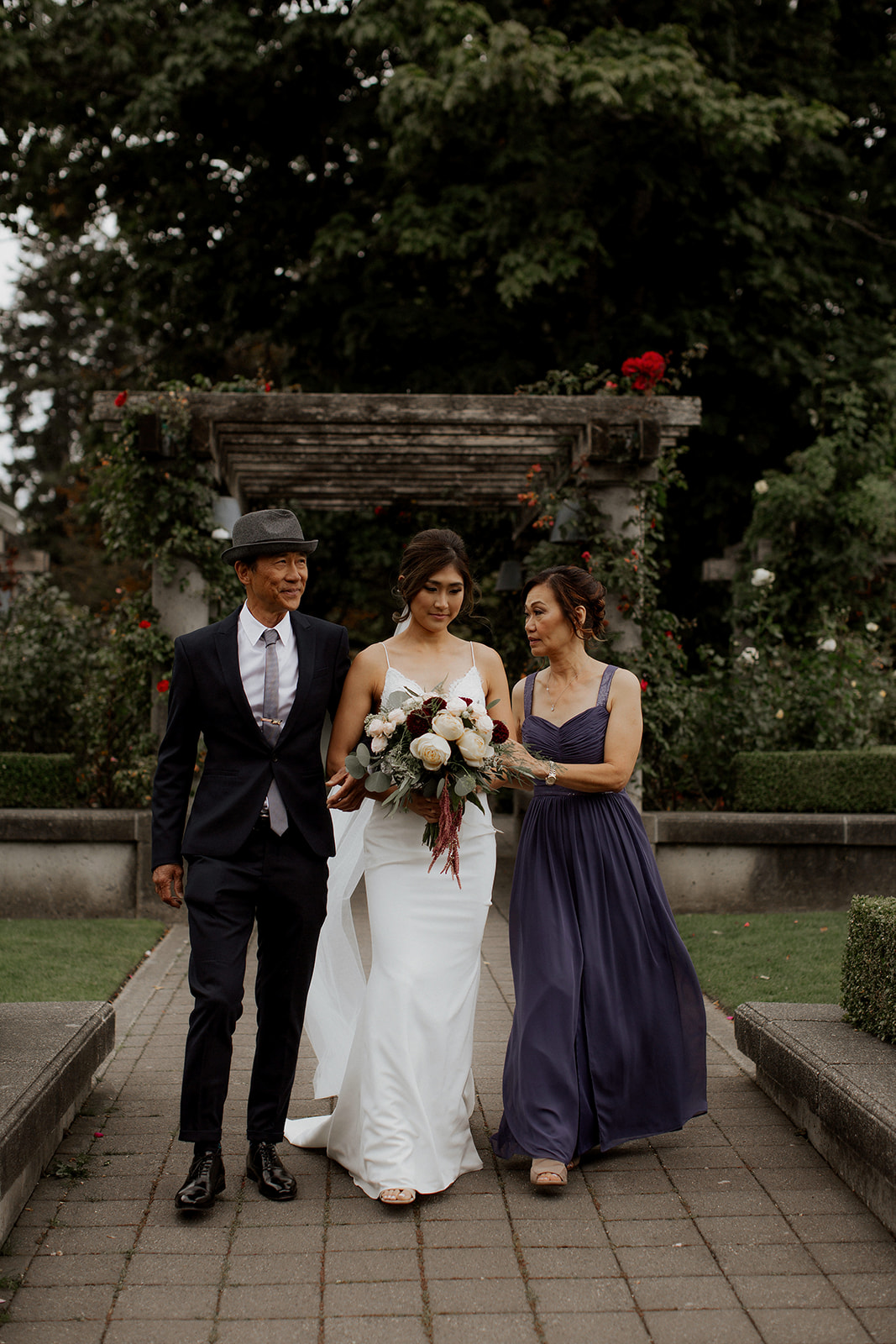 Bride is walked down the aisle by both parents at UBC Rose Garden Ceremony