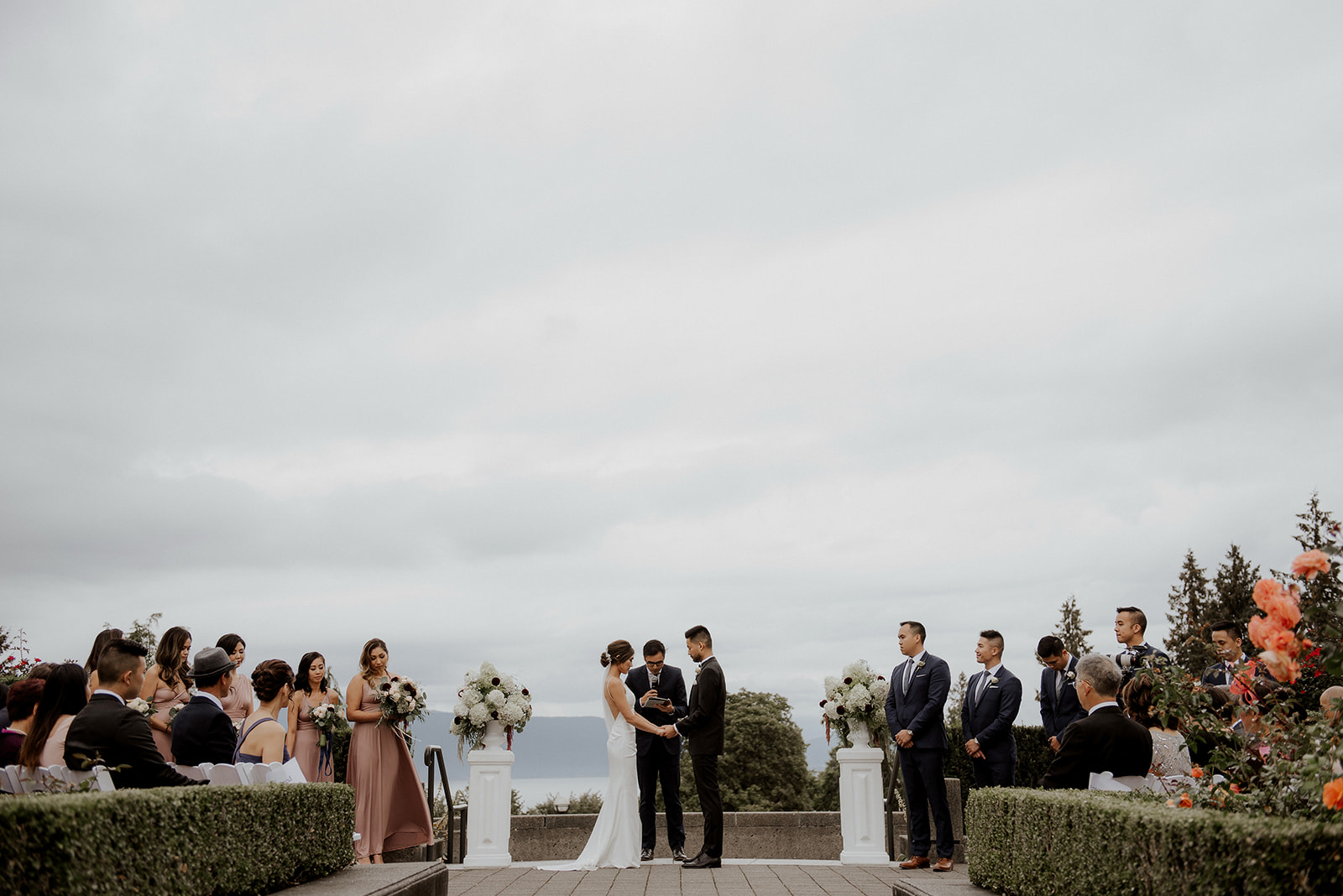 Newlyweds stand in front of guests at UBC Rose Garden by Kaoverii Silva Photography