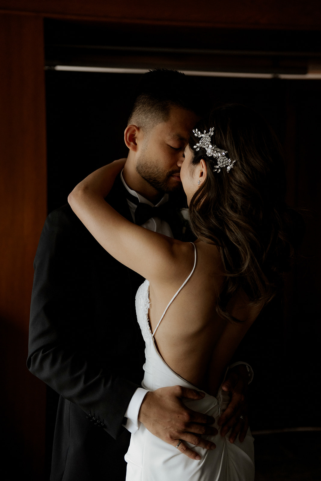 Newlyweds embrace and kiss in the shadows by Kaoverii Silva Photography