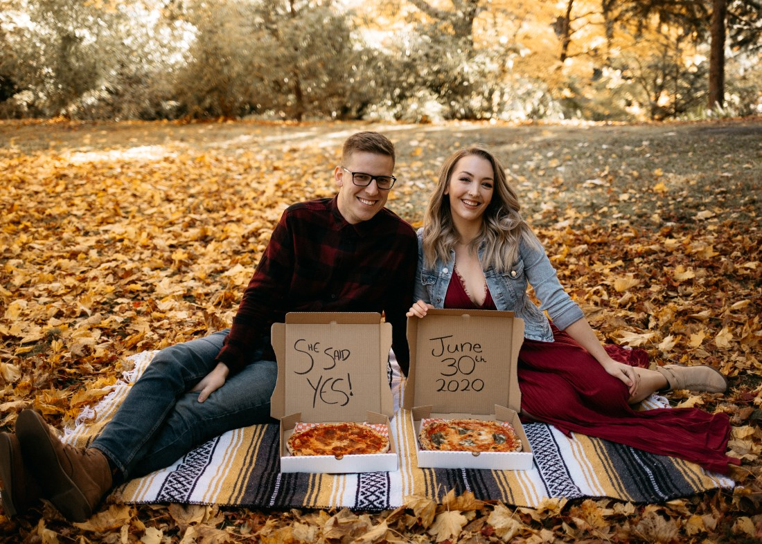 Engaged Couple sit in fall leaves with pizza boxes announcing date