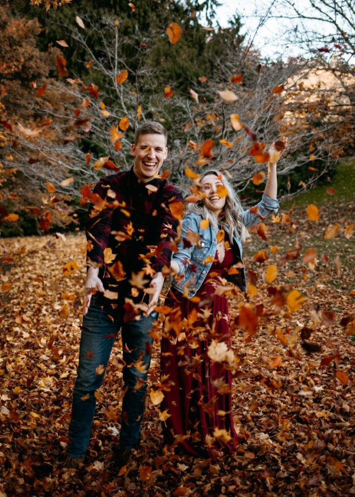 Autumn Engagement Session couple throw fall leaves in the air at Hatley Castle