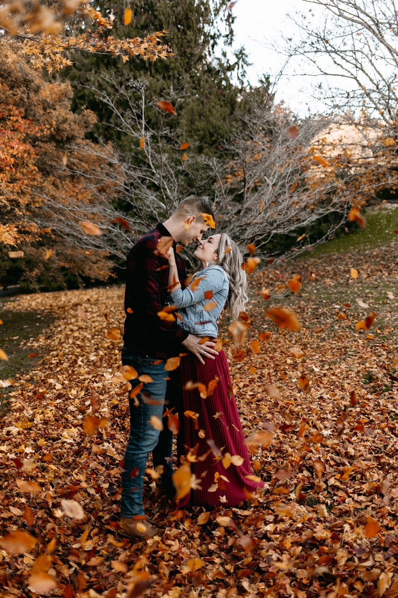 Couple embrace surrounded by autumn leaves on Vancouver Island