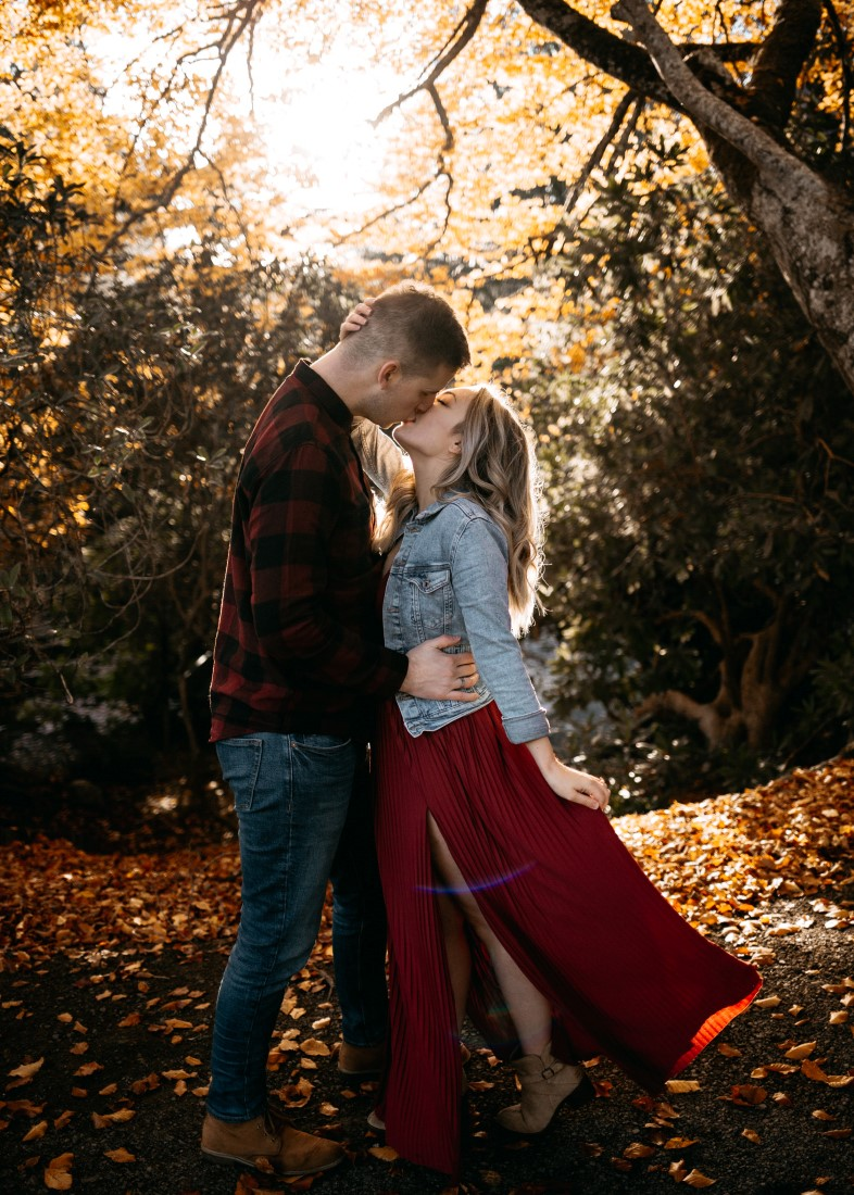 Bride to be in jean jacket and burgundy dress kissed by husband to be Evergrey Photography