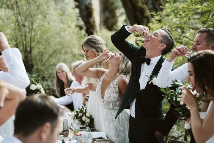 Bride and groom drink a toast at forest wedding reception by Truffles Catering Vancouver Island