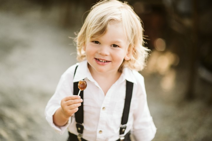 Little boy eats cake pop with a smile by Truffles Catering Vancouver Island