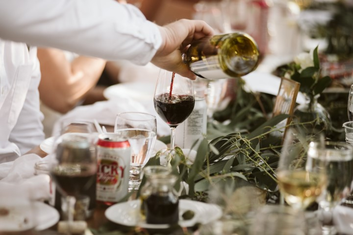 Servers pour wine for guests at forest wedding reception by Truffles Catering Vancouver Island