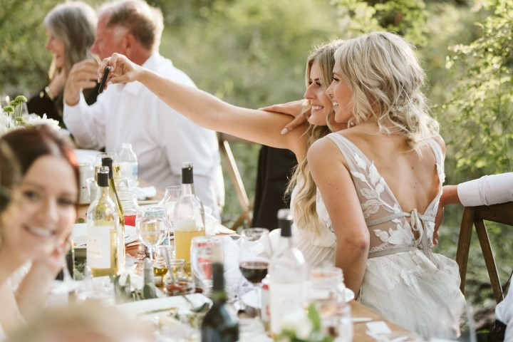 Bride and friend taking a selfie at forest wedding reception
