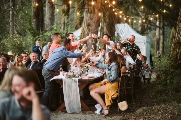 Guests toast the bride and groom at forest reception on Vancouver Island