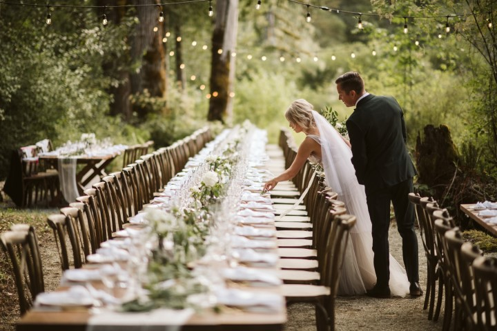 Bride and groom set name cards on long table wedding reception tables in the forest
