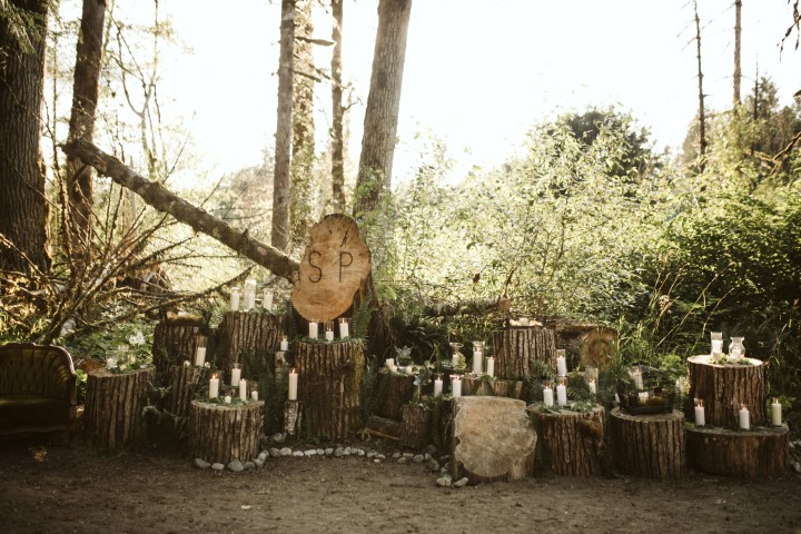 Logs with candles on top at a forest wedding by Erin Wallis Photography