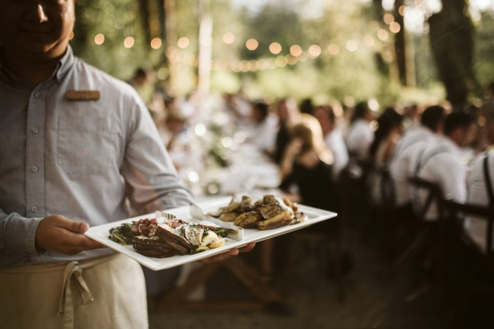 Waiter serves wedding main course to forest reception long table Truffles Catering Vancouver Island