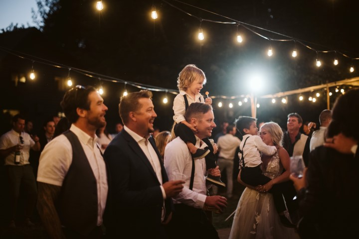 Wedding Guests watch as newlyweds have their first dance under cafe lights