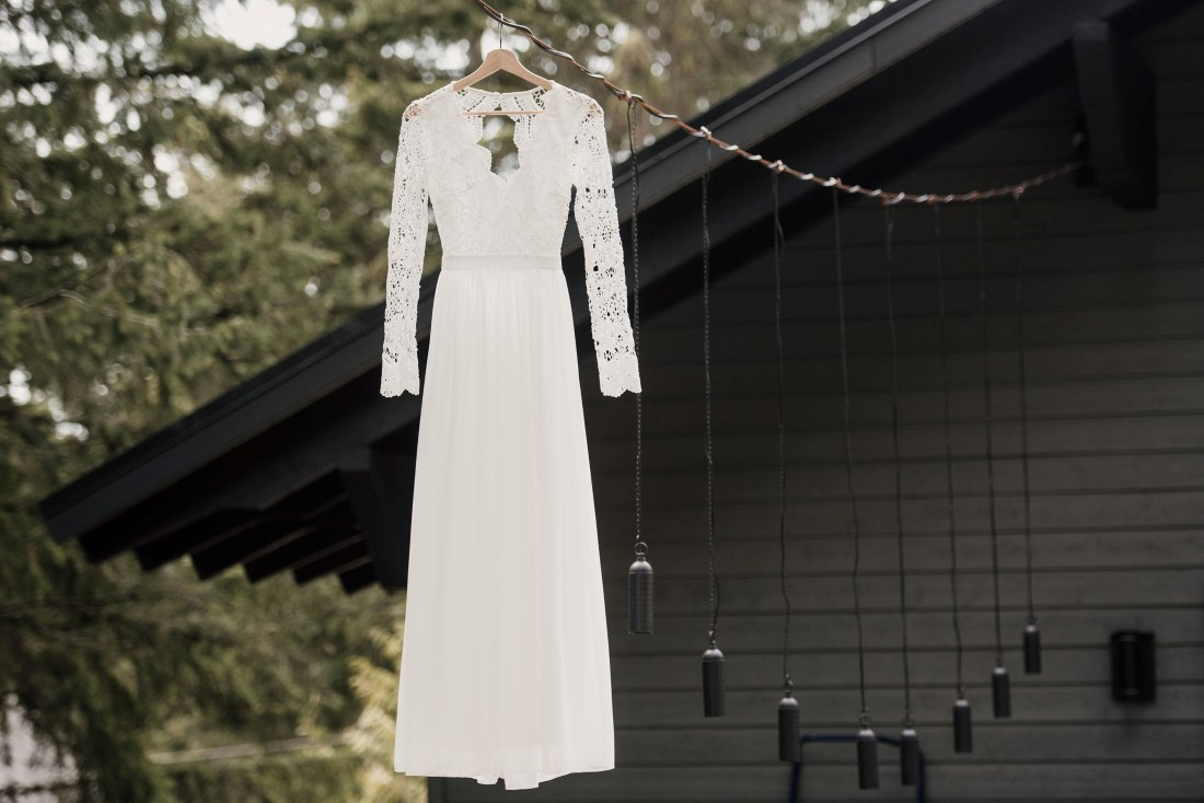Bridal gown hangs from a tree by West Coast Weddings Magazine