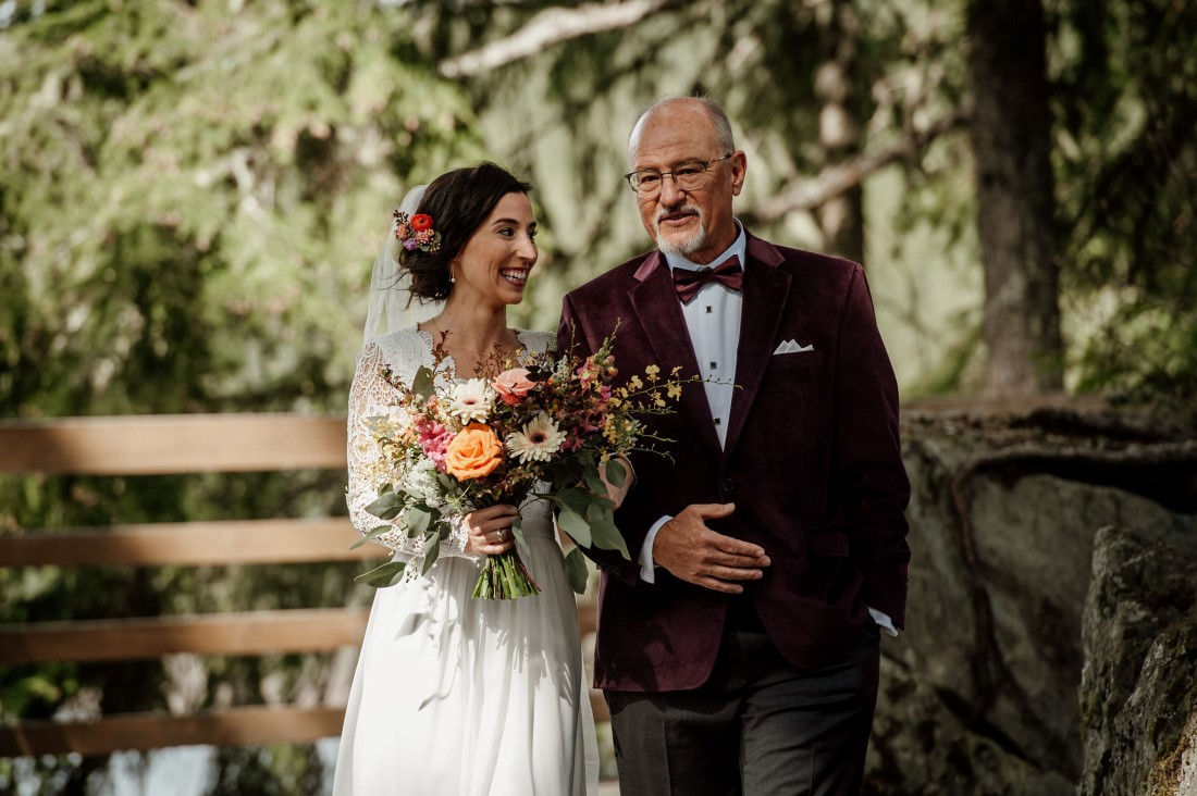 Father walks bride down the aisle at Stone Circle in Whistler with bouquet by Senka Florist