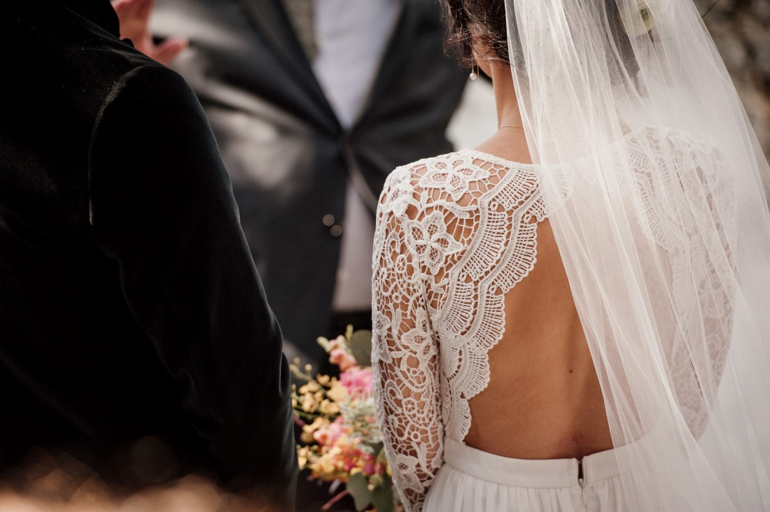 Bride wears lace bodice with back cut out and long veil by Emily Serrell