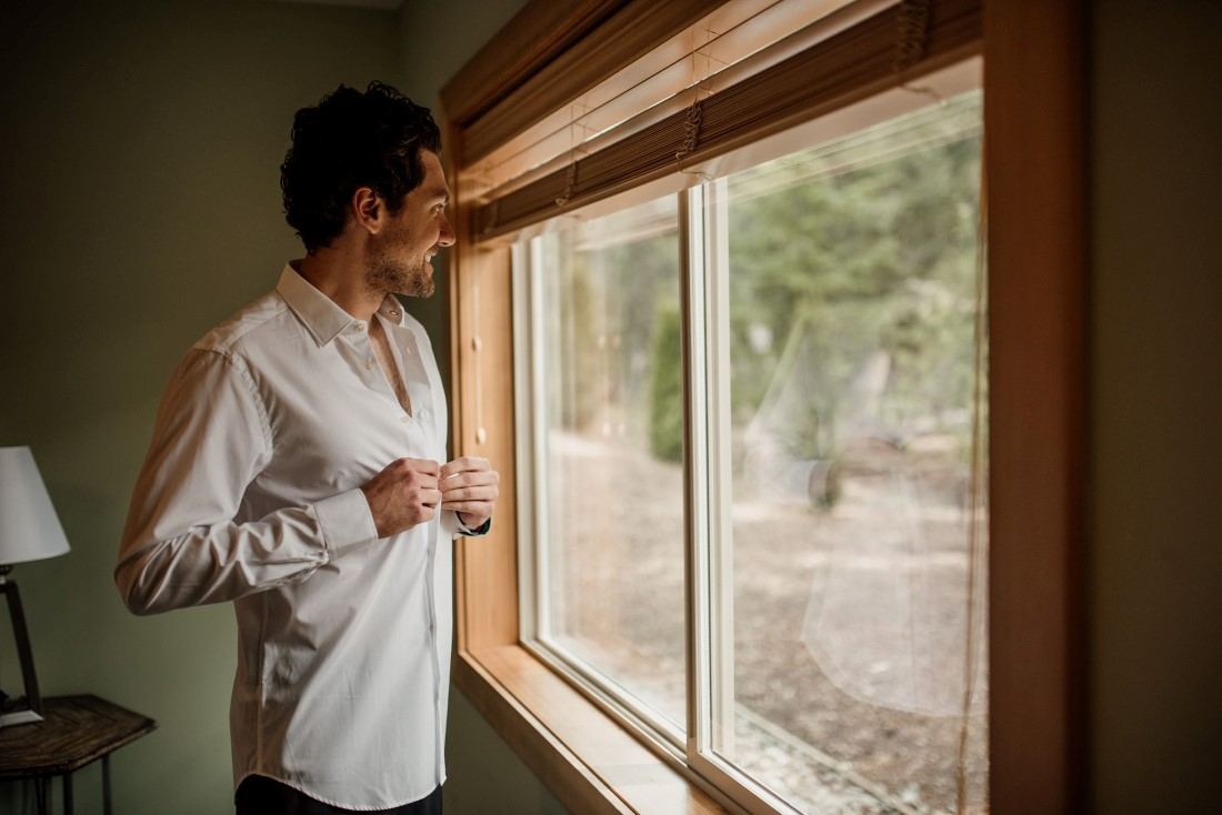Groom buttons his shirt while looking out a window near Stone Circle Whistler