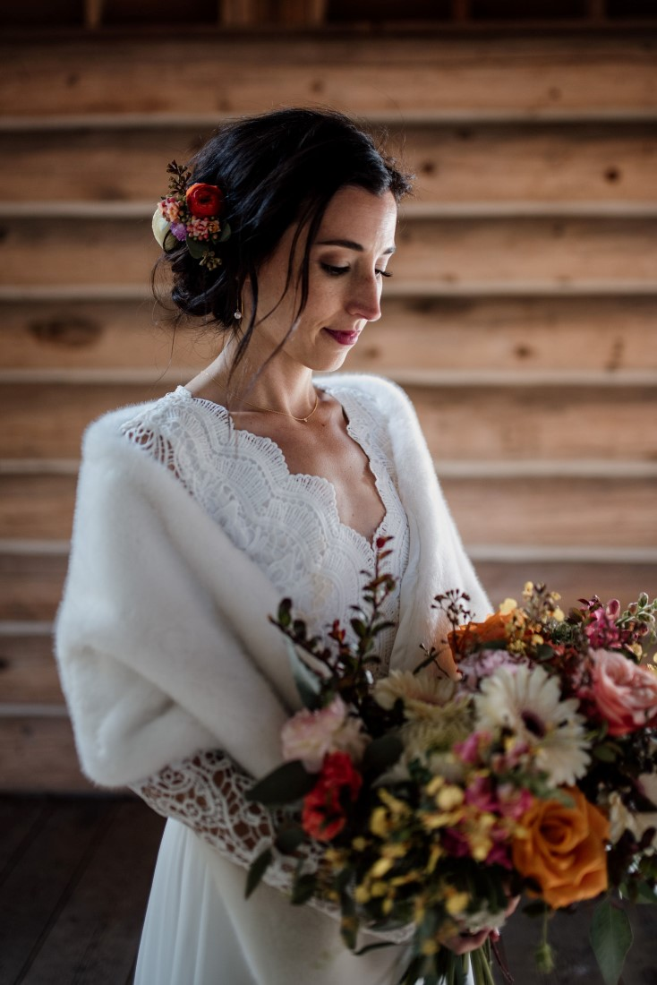 Bride in white stole looks down at bouquet of orange and yellow flowers by Senka Flowers and makeup and hair by Kerry Waring