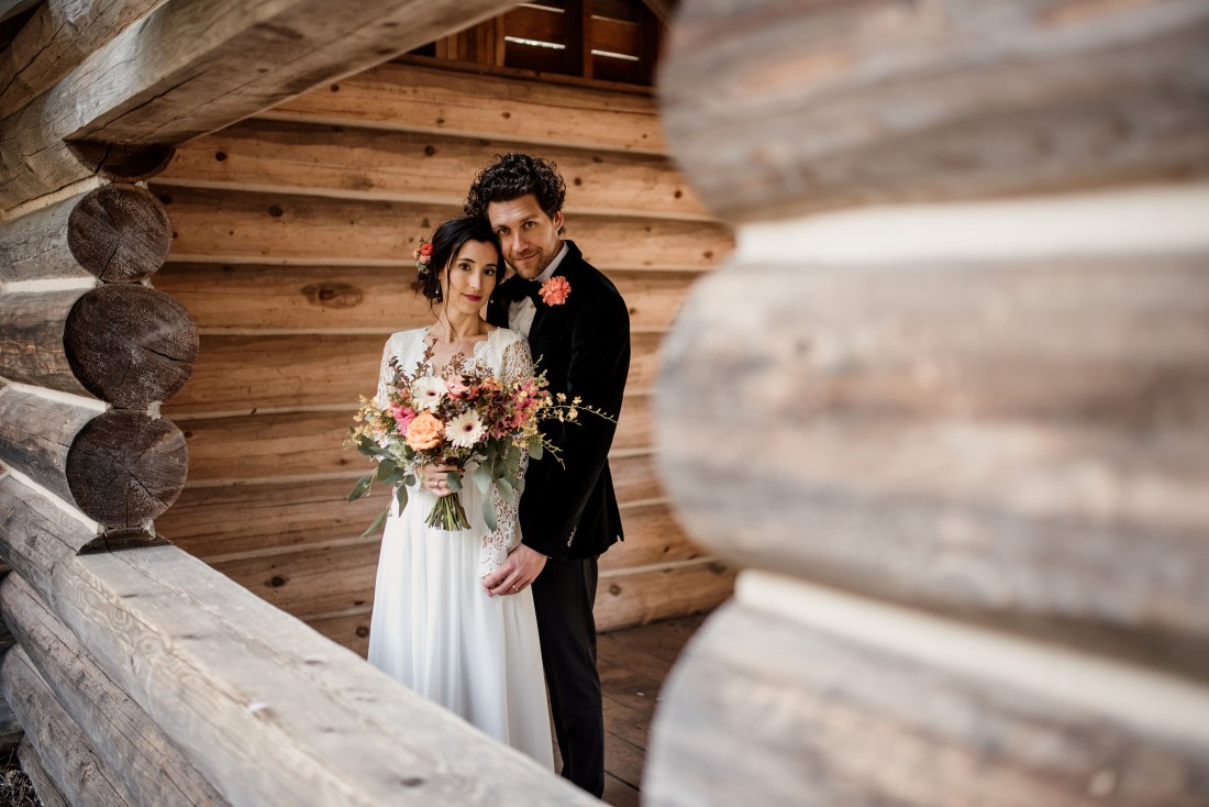 Stone Circle Whistler newlyweds pose by log wall by Emily Serrell