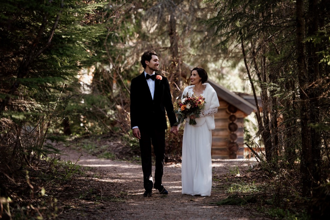 Newlyweds meander down forest path near Stone Circle Whistle by West Coast Weddings Magazine