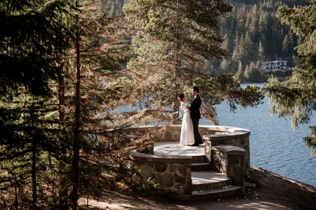 Stone Circle Whistler Wedding Couple stand among fir trees with lake behind