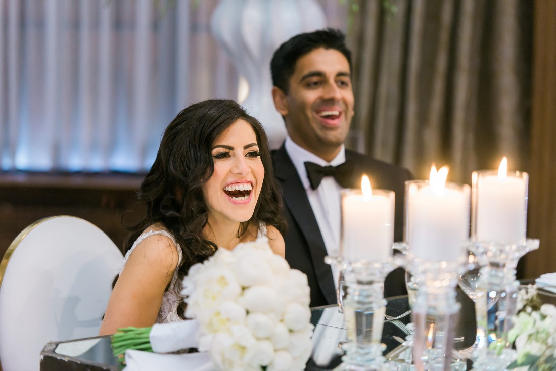 Bride and Groom laugh at speeches while seated at head table with candles and white roses at Vancouver Club