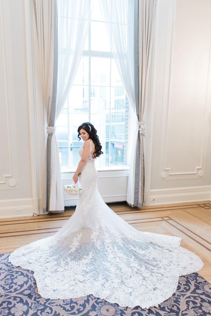 Bride with lace train spread around Bisou Bridal Martina Liana Design