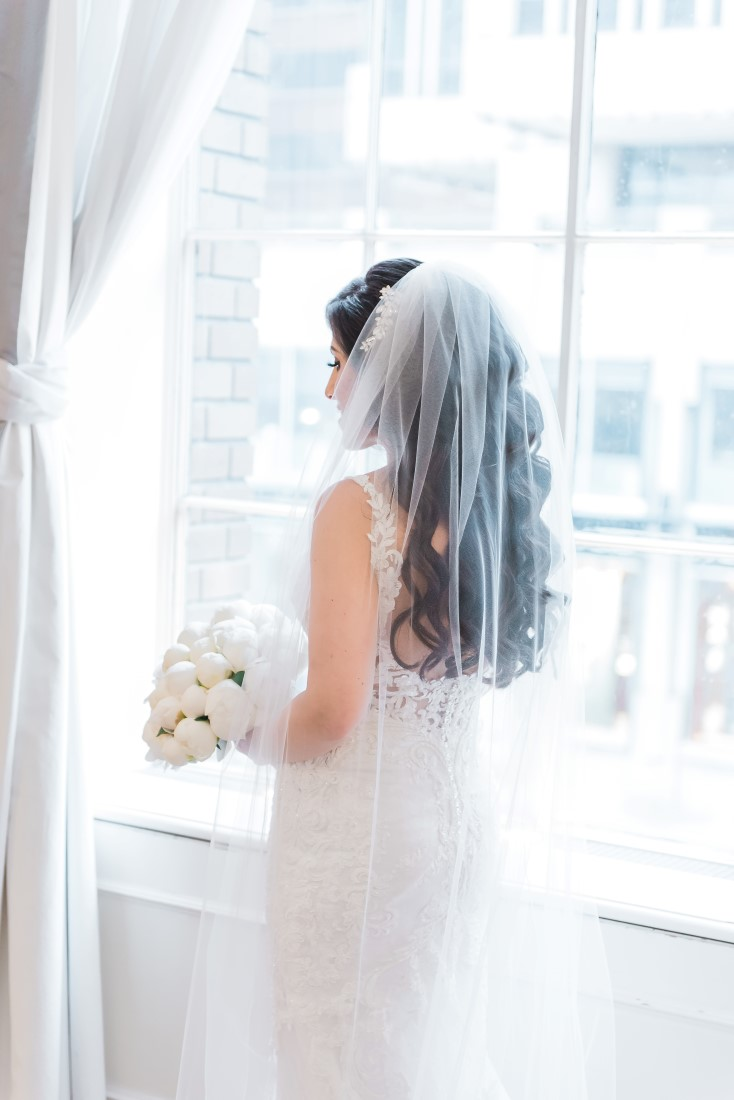 Bridal veil over long curls and holding white rose bouquet by Tala Florist