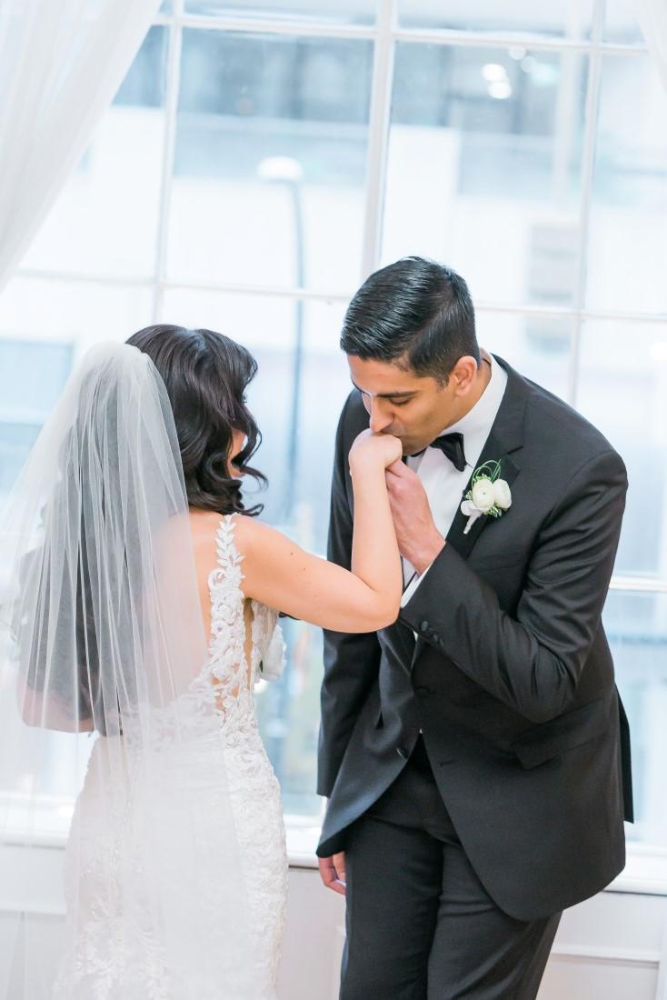Groom kisses brides hand by L'Estelle Photography