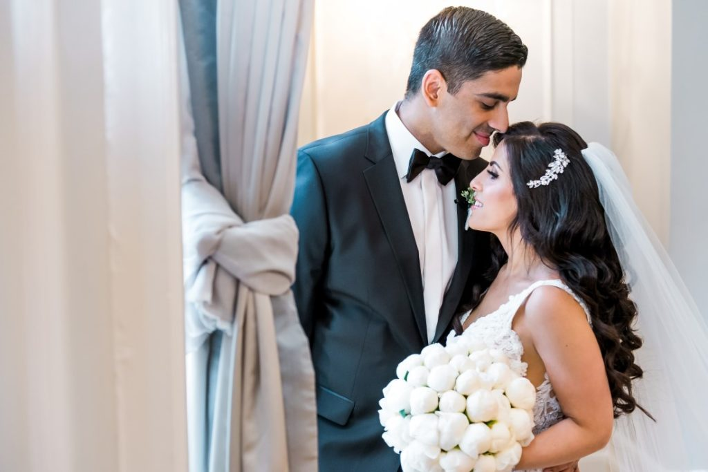 Newlyweds portrait at Vancouver Club with bridal bouquet of white peonies by Tala Florist